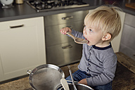Toddler boy sitting on the kitchen table playing with wooden spoon - LITF000347