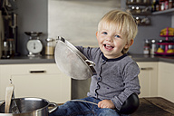 Portrait of smiling toddler boy sitting on the kitchen table playing with strainer - LITF000350