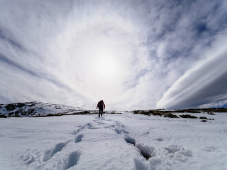 Spain, Sierra de Gredos, man hiking in snow - LAF001631