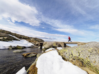 Spain, Sierra de Gredos, hiker crossing brook in mountains - LAF001634