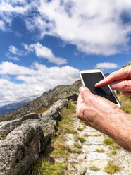Spain, Sierra de Gredos, hiker with cell phone on trail - LAF001640