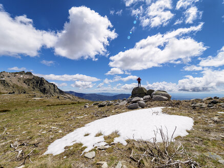 Spain, Sierra de Gredos, hiker standing on rock in mountainscape - LAF001643
