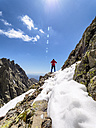Spain, Sierra de Gredos, hiker standing on rock in mountainscape - LAF001649