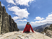 Spain, Sierra de Gredos, hiker sitting on rock in mountainscape - LAF001652