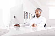 Portrait of businessman working at computer in the office - MFRF000619