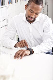 Businessman adjusting his smartwatch - MFRF000622