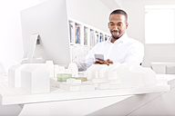 Architectural model on a desk at office with man looking at his smartphone in the background - MFRF000625