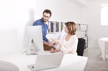 Two colleagues discussing their work in an office - MFRF000634