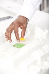 Man's hand putting building block on architectural model, close-up - MFRF000640