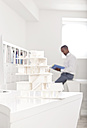 Architectural model on desk in an office with reading man in the background - MFRF000643