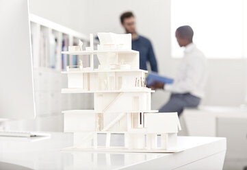 Architectural model on desk in an office with two talking people in the background - MFRF000646