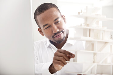 Portrait of smiling man looking at architectural model - MFRF000655