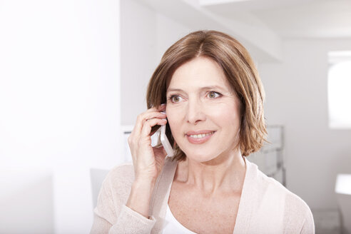 Portrait of smiling woman telephoning with smartphone in the office - MFRF000670