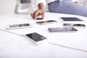Smartphones lying on construction plan - MFRF000676