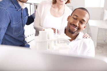 Smiling man presenting architectural model at video conference - MFRF000679