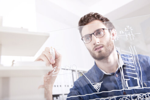 Portrait of young man drawing on glass pane in an office - MFRF000688