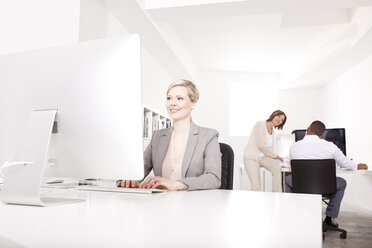 Businesswoman working at desk in the office while her colleagues talking in the background - MFRF000691