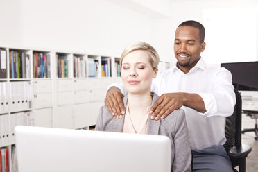 Man massaging his colleague in the office - MFRF000697