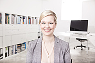 Portrait of smiling blond businesswoman in the office - MFRF000700