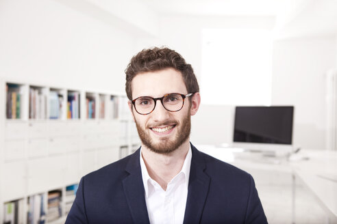 Portrait of smiling businessman in the office - MFRF000703