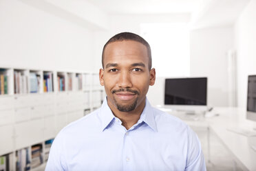 Portrait of smiling businessman in the office - MFRF000706