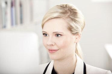 Portrait of blond businesswoman working at computer - MFRF000712
