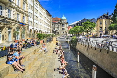 Germany, Bavaria, Bayreuth, people sitting on steps at canal in summer - VT000529