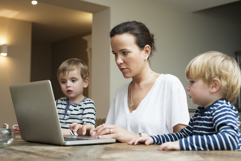 Mother using laptop with her sons sitting next to her - LFOF000245