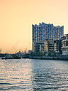 Germany, Hamburg, Elbphilharmonie at sunset with multi-family houses in the foreground - KRPF001748