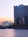 Germany, Hamburg, Elbphilharmonie and driving cruise liner at sunset - KRPF001751