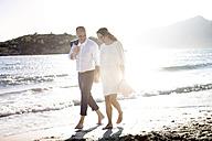 Spain, Majorca, pregnant woman and man walking on beach - GDF000996