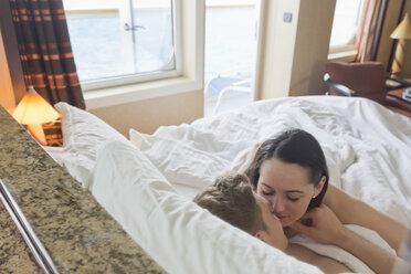 Young couple on cruise cuddling in bed - ONBF000007