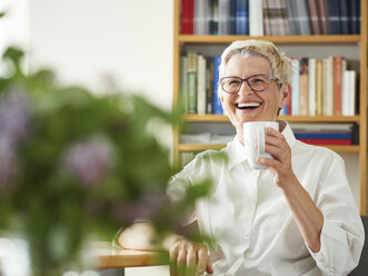Portrait of laughing senior woman with cup of coffee at home - DISF002485