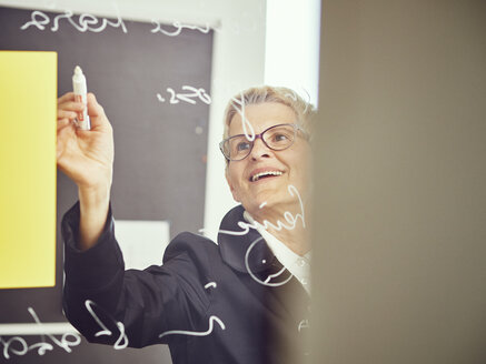 Woman writinging on glass pane in a classroom - DISF002494