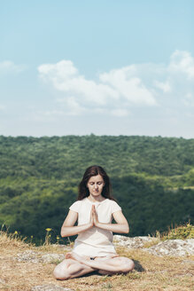 Young woman meditating on the cliff - BZF000290