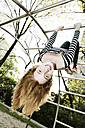 Portrait of smiling girl hanging upside down on jungle gym - JATF000862