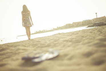 Spain, Tenerife, young woman standing on the beach, flip-flops in the foreground - SIPF000515