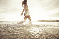 Spain, Tenerifa, young woman running into water against the sun - SIPF000521