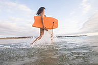 Spain, Tenerife, young woman running with swimming board into water - SIPF000524