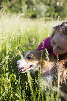 Italy, Lecco, teenage girl with her dog on a meadow - MRAF000055