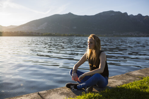 Italy, Lecco, thoughtful teenage girl sitting on the edge of the lake - MRAF000061