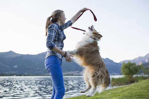 Italy, Lecco, teenage girl playing with her dog at lakeshore - MRAF000064