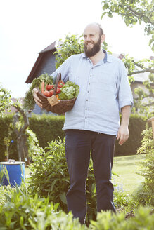 Young man standing in garden, basket with fresh vegetables - SEGF000552