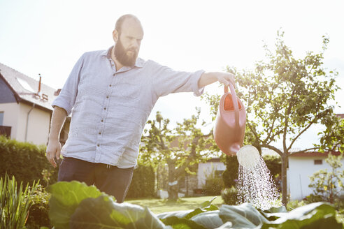 Young man working in garden, watering with watering can - SEGF000555