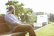 Young man sitting on bench in garden, drinking a beer - SEGF000564