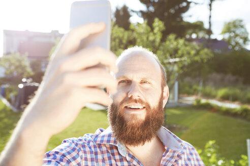 Young man with smartphone in garden, selfie - SEGF000567