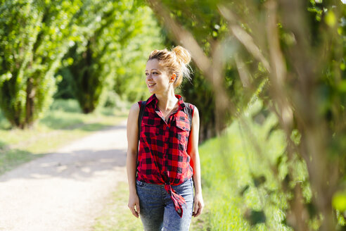 Smiling woman walking in nature - GIOF001132