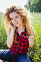 Portrait of woman sitting in a field hearing music with earphones - GIOF001135