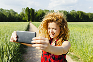 Woman taking selfie with smartphone in nature - GIOF001147