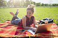 Smiling woman lying on blanket on a meadow using laptop - GIOF001153